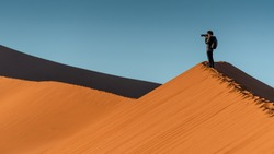 Young male traveler and photographer standing on the top of sand dune photographing sunrise or sunset in desert of Namibia, Africa. Travel photography concept