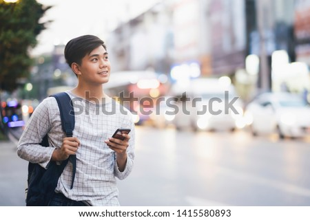 Young male traveler with backpack walking through city street using mobile phone to searching GPS online maps application.  Online technology lifestyle  traveling and communication concept.   #1415580893