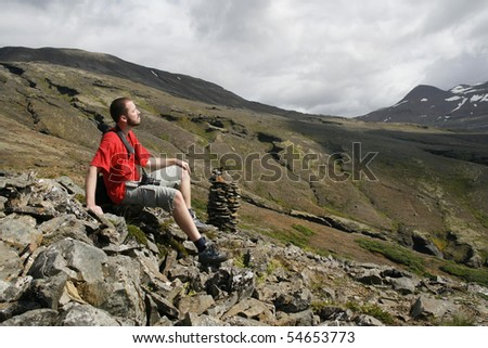 Young male traveller, photographer resting and enjoying the beautiful view of mountains in Iceland
