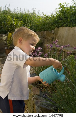 Young male watering garden. Toy watering can used to sprinkle herb garden.