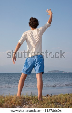 Young male waving hands at sea side