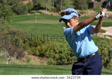 Young male with blue shirt about to hit a ball on a beautiful golf course with flag visible, focus on golfer
