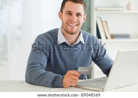 Young male with credit card at his laptop