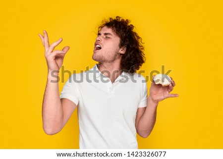 Young male with curly hair keeping eyes closed and gesturing with hand while tasting marvelous donut against vibrant yellow background #1423326077