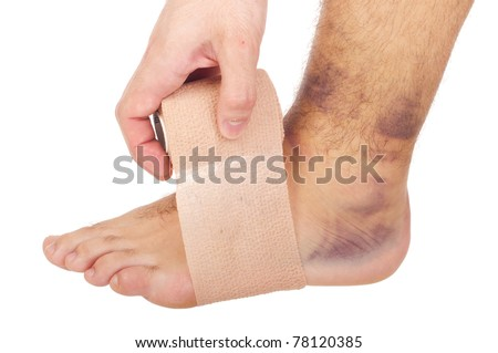 young male with sprained ankle applying medical bandage (isolated on white background)