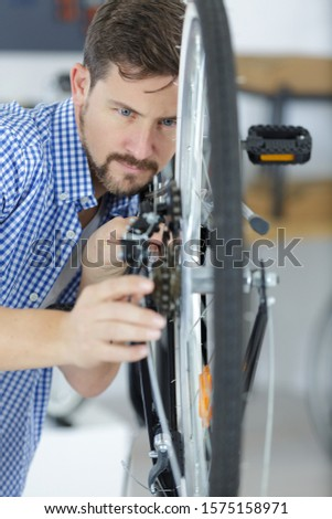 young male worker fixing a bike