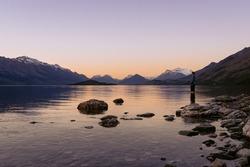 Young man admiring the beuaty in Lake Wakatipu sunset. New Zealand, South Island landscape