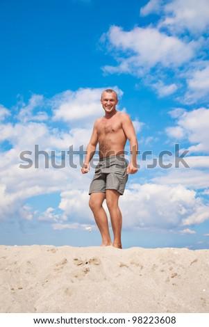 young man against a blue sky on a beach