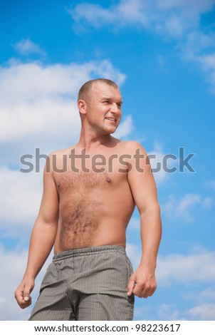 young man against a blue sky on a beach