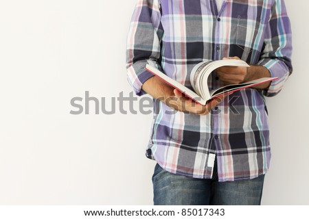 Young man against the wall reading a book