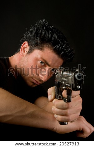 Young man aiming and firing a deadly weapon