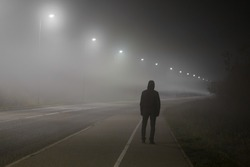 Young man alone slowly walking under white street lights in night. Dark time. Peaceful atmosphere in mist. Foggy air. Back view.