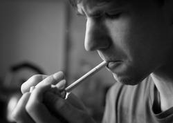 young man alone smokes cigarettes