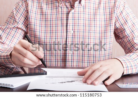 Young man analyze som document with pen in his hand and using tablet PC