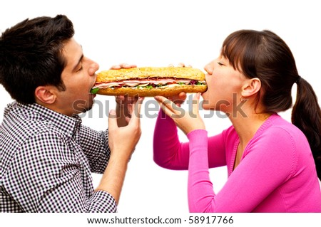 young man and a woman eating sandwich from two sides isolated on white