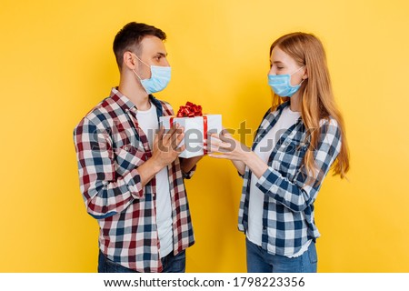young man and a woman in plaid shirts and medical protective masks, a happy man gives a gift to his girlfriend, on an isolated yellow background