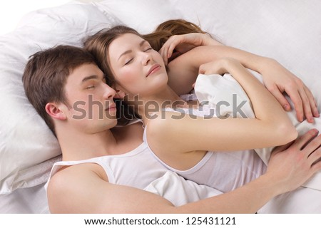 Young man and beautiful woman sleeping in a white bedding