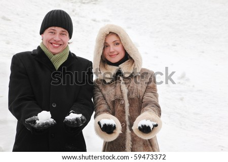 young man and girl in warm dress smiling and holding snowballs, half body, winter day