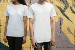 Young man and girl in white T-shirts standing on the street