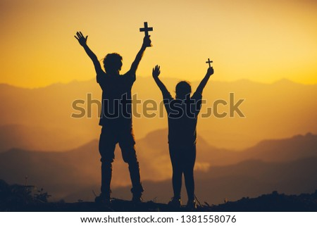 Young man and girl standing holding christian cross for worshipping God at sunset background. christian silhouette concept.