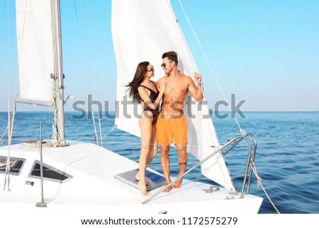 Young man and his beautiful girlfriend in bikini on yacht. Happy couple during sea trip #1172575279