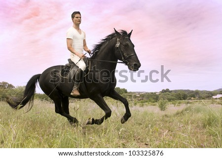 young man and his black stallion in  a field
