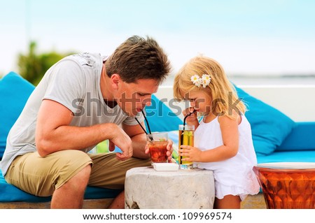 young man and his daughter drinking exotic cocktails at beach cafe
