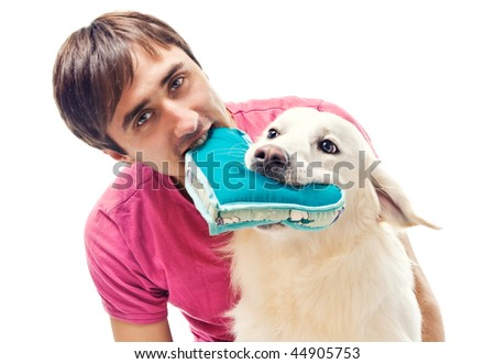 Young man and his dog fighting over a heart shaped pillow