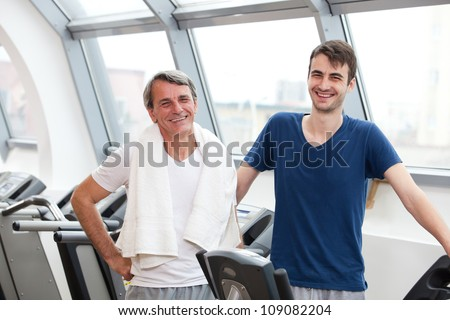 young man and his father training in the gym, laughing, treadmill
