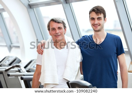 young man and his father training in the gym: treadmill, smiling
