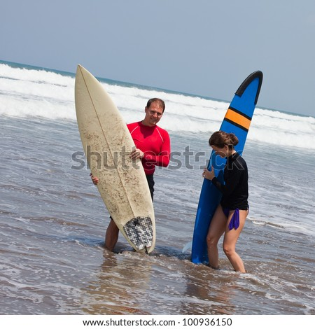 young man and the girl with boards for surf on an ocean coast