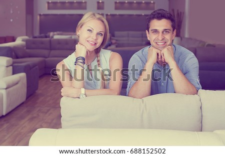 Young man and wife are happy of the purchase of a new sofa in the shop