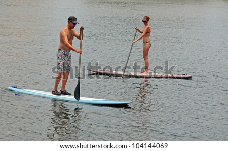 young man and woman couple paddle boarding in ocean