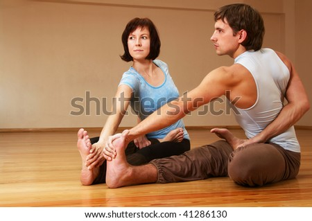 young man and woman doing yoga indoor
