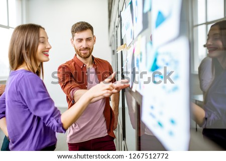 Young man and woman dressed casually working with some statistics on the glass wall in the office