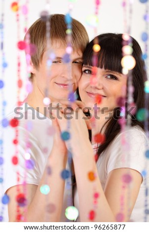 Young man and woman dressed in white shirts hold hands behind transparent curtain of beads; focus on pair