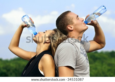 Young man and woman drinking water from a bottle