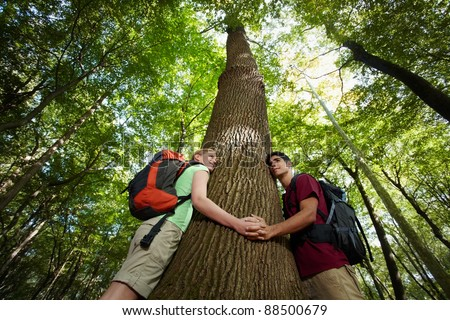 young man and woman during hiking excursion, hugging tree and holding hands. Horizontal shape, low angle view, waist up