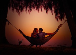 Young man and woman enjoying each other in a hammock on the tropical beach
