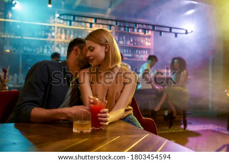 Photo of  Young man and woman flirting in the bar, enjoying drinks and conversation. Love, couple, romance concept. Selective focus. Horizontal shot