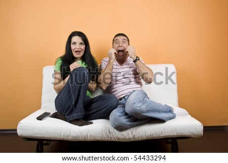 Young man and woman ,friends watching TV  a horror movie and they are scared