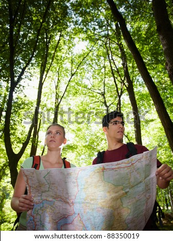 young man and woman got lost during hiking excursion and look for destination on map. Vertical shape, waist up