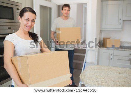Young man and woman holding boxes in their hands to relocate