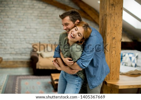 Young man and woman hugging standing at home interior and tender husband embracing wife gently #1405367669