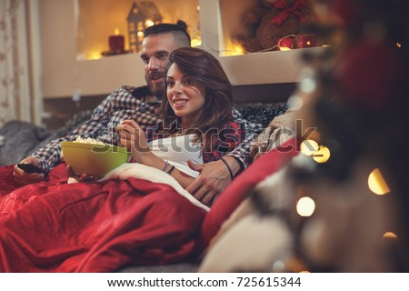 Young man and woman in bed watching tv and eating pop corn