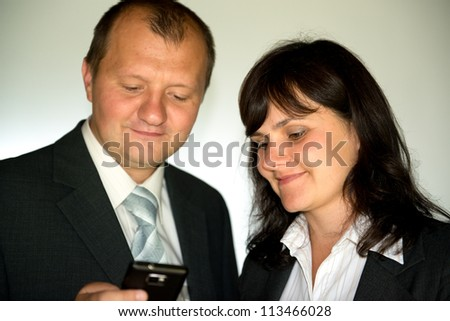 young man and woman in business suits look at smart phone, focus on womans eyes