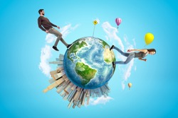 Young man and woman in casual clothes walking on small planet Earth with modern city popping up on one side and hot-air balloons flying in sky. Explore world. Travel more. Build world of your dream.
