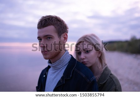 Young man and woman in casual outfits looking away while standing on lake shore against cloudy sundown sky #1503855794