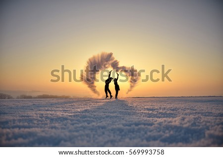 Young man and woman in love make fun in cold winter morning with hot water who freezes in the cold air. Valentine photo with space for your montage