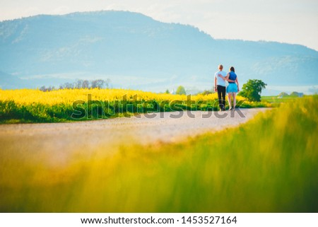 Young man and woman in love walking together through spring colorful landscape. White edit space #1453527164